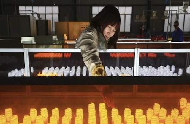 Trabajadora china en industria de bombillas
